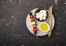 蕃茄、蒜味咸腊肠、无盐干酪、蓬蒿叶子和薄荷的意大利式饺子,在回合的maslik可口开胃菜串  库存图片