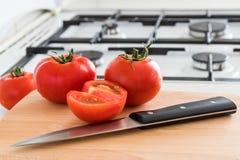 蕃茄和刀子在木板 免版税库存照片