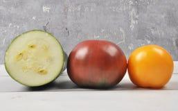 蕃茄和夏南瓜在被风化的木头 免版税库存照片