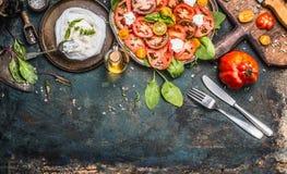 蕃茄和无盐干酪沙拉,在黑暗的准备变老了土气背景,顶视图 意大利午餐 免版税库存图片
