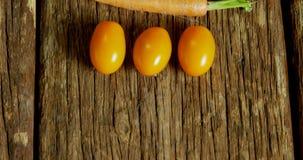 蕃茄和红萝卜在木桌4k上安排了 股票视频