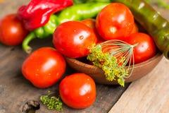 蕃茄和胡椒在碗在木桌上 免版税库存照片