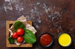 蕃茄和蓬蒿离开与调味汁顶视图 免版税库存照片
