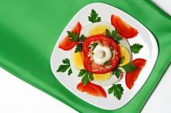 蕃茄和鸡蛋沙拉在一块白色板材和一块绿色餐巾 库存图片