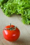 蕃茄和莴苣在木背景 库存图片