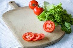 蕃茄和莴苣在木背景 免版税库存照片