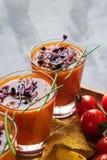 蕃茄在玻璃的汤gazpacho用发芽的新芽伴随于在浅灰色的背景的玉米片 垂直 饮食和 库存图片