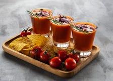 蕃茄在玻璃的汤gazpacho用发芽的新芽伴随于在浅灰色的背景的玉米片 垂直 饮食和 免版税图库摄影