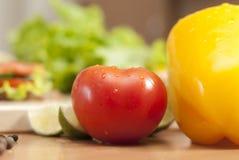 蕃茄在蔬菜包围的厨房里 免版税库存照片