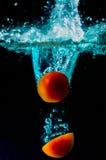 蕃茄在黑背景的水飞溅 库存照片