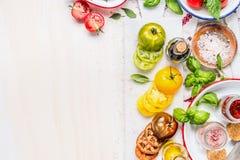 蕃茄沙拉准备 烹调在白色大理石切板的蕃茄成份 在白色的各种各样的五颜六色的切的蕃茄 免版税图库摄影
