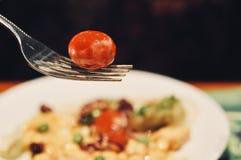蕃茄特写镜头画象在叉子的有沙拉模糊的背景  免版税库存图片
