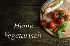 蕃茄用在木桌,文本Heute Vegetarisch上的面包 免版税图库摄影