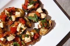 蕃茄蓬蒿乳酪在晴朗的室外桌上的bruschetta开胃菜 库存图片