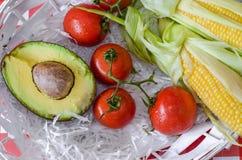蕃茄鲕梨、分支和甜玉米两个玉米棒在白色木篮子的与秸杆 库存图片