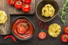 蕃茄,西红柿酱,面团,迷迭香,烹调的盘红辣椒在黑暗的背景 顶视图 免版税库存照片
