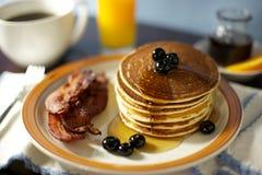 薄煎饼、烟肉和莓果早餐用咖啡和汁液 图库摄影