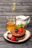 薄煎饼、蜂蜜、莓果和牛奶 鲜美的早餐 图库摄影