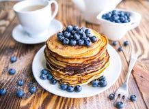薄煎饼健康早餐用蓝莓、沼泽越橘、杯子绿茶,杯子蓝莓和茶壶 免版税库存图片