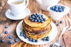 薄煎饼健康早餐用蓝莓、沼泽越橘、杯子绿茶,杯子蓝莓和茶壶 免版税图库摄影
