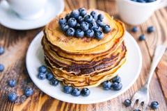 薄煎饼健康早餐用蓝莓、沼泽越橘、杯子绿茶,杯子蓝莓和茶壶 图库摄影