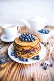 薄煎饼健康早餐用蓝莓、沼泽越橘、杯子绿茶,杯子蓝莓和茶壶 库存照片