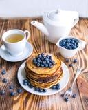 薄煎饼健康早餐用蓝莓、沼泽越橘、杯子绿茶,杯子蓝莓和茶壶 库存图片