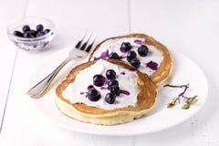 薄煎饼冠上用乳脂干酪蜂蜜和蓝莓在板材白色背景自创鲜美薄煎饼鲜美早餐 免版税图库摄影