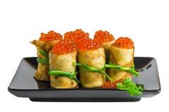 薄煎饼劳斯用在黑色的盘子的鱼子酱 免版税图库摄影