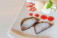 薄煎饼和果子与冰淇凌在桌上 免版税库存图片