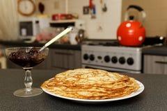 薄煎饼和果酱在厨房的背景 免版税库存图片