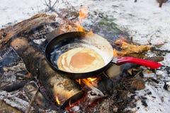 薄煎饼在一个煎锅的火烹调了有一支红色笔的 免版税库存图片