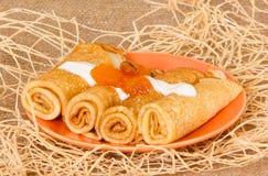 薄煎饼在卷滚动了用杏子果酱和奶油 在橙色板材上 在装饰背景的油煎的酥皮点心 免版税库存图片