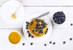 薄煎饼堆浇灌了用蜂蜜,并且在白色的蓝莓求爱 图库摄影