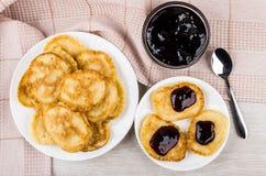 薄煎饼堆用果酱和茶匙在桃红色毛巾 免版税库存图片