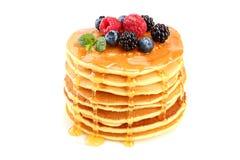 薄煎饼堆积用不同的在白色背景隔绝的莓果和蜂蜜 免版税库存照片