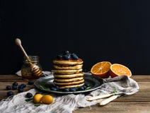 薄煎饼塔用新鲜的蓝莓、桔子和薄菏在一土气金属片 免版税库存图片