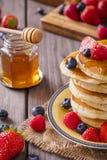 薄煎饼塔用蜂蜜和莓果特写镜头 库存图片