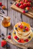 薄煎饼塔用蜂蜜和莓果 免版税库存照片