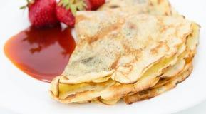 薄煎饼外壳接近的看法用草莓和果酱在白色 免版税图库摄影