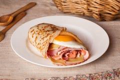 薄煎饼早餐用火腿和鸡蛋在一幅土气静物画 免版税库存照片
