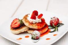 薄煎饼点心用草莓和奶油在白色 库存图片