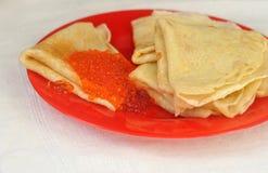 薄煎饼用在一块红色板材的红色鱼子酱 免版税库存图片