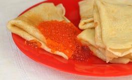薄煎饼用在一块红色板材的红色鱼子酱 免版税库存照片