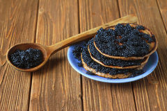 薄煎饼用在板材,在桌上的一把木匙子的黑鱼子酱 免版税图库摄影