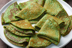 薄煎饼用在白色板材的菠菜 免版税库存照片