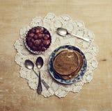 薄煎饼用在老被仿造的餐巾的果酱在木桌上 免版税库存照片
