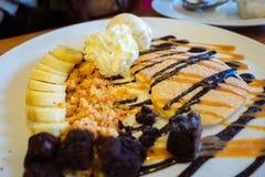 薄煎饼用巧克力汁和冰淇凌,香蕉,果仁巧克力 免版税库存照片