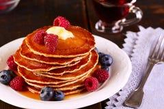 薄煎饼用新鲜的莓果和枫蜜在木桌上 免版税库存图片