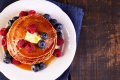 薄煎饼用新鲜的莓果枫蜜和黄油在木桌上 免版税库存图片